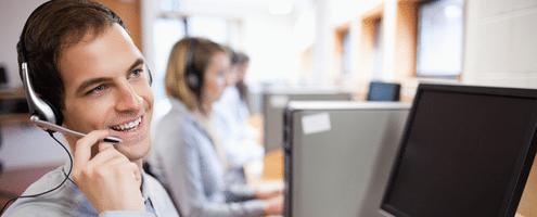 Mitarbeiter vom IT-Service mit Headset am PC