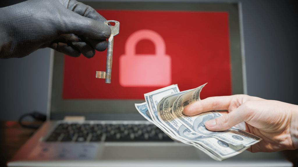 Hand mit Handschuh und Schlüssel andere Hand mit Geldscheinen und Laptop mit Schloss auf Bildschirm im Hintergrund als Symbol für Ransomware